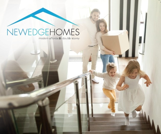 Couple carrying boxes while children climbing stair ways in their new home