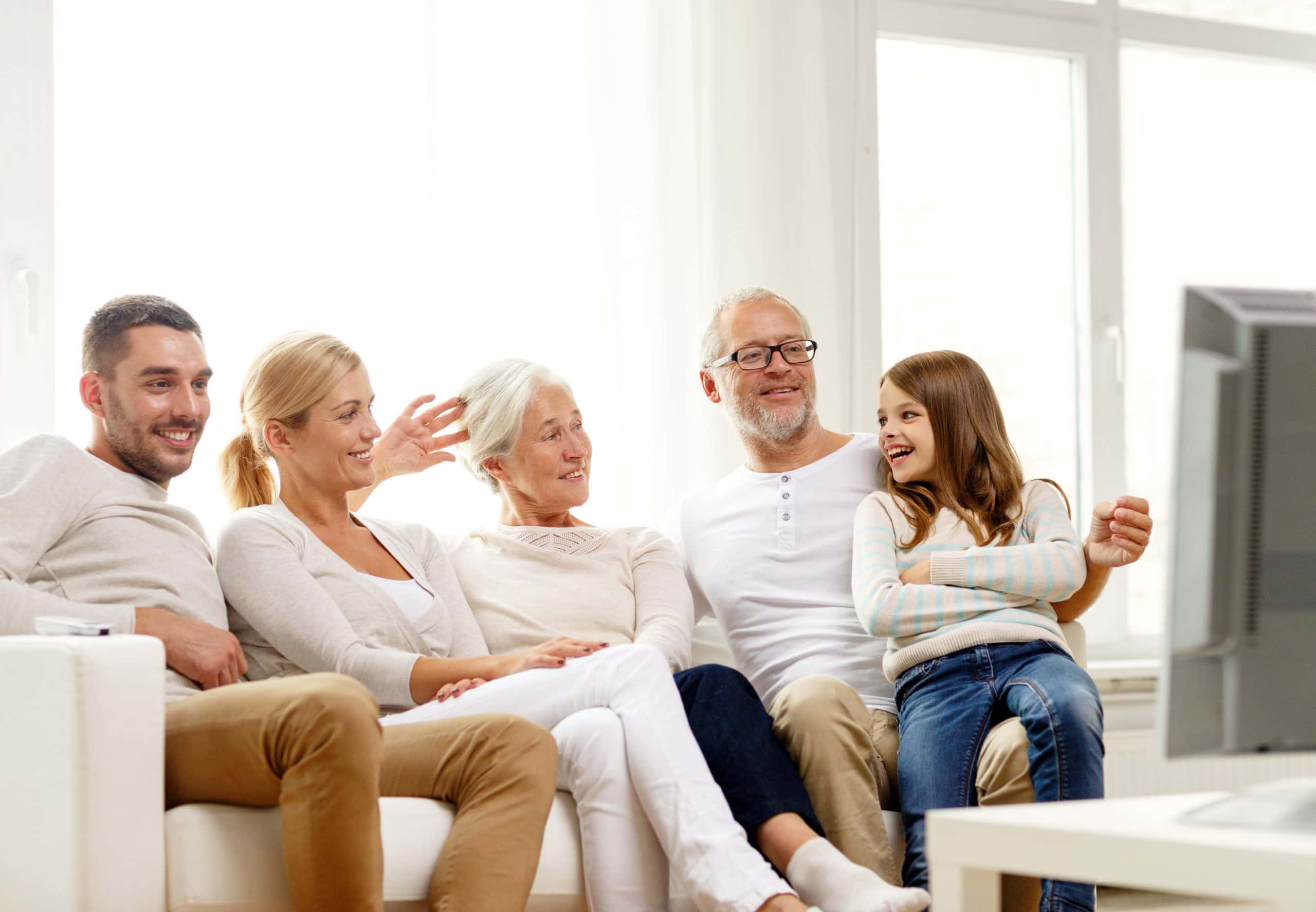 Happy Family sitting on sofa and watch tv at their granny flat