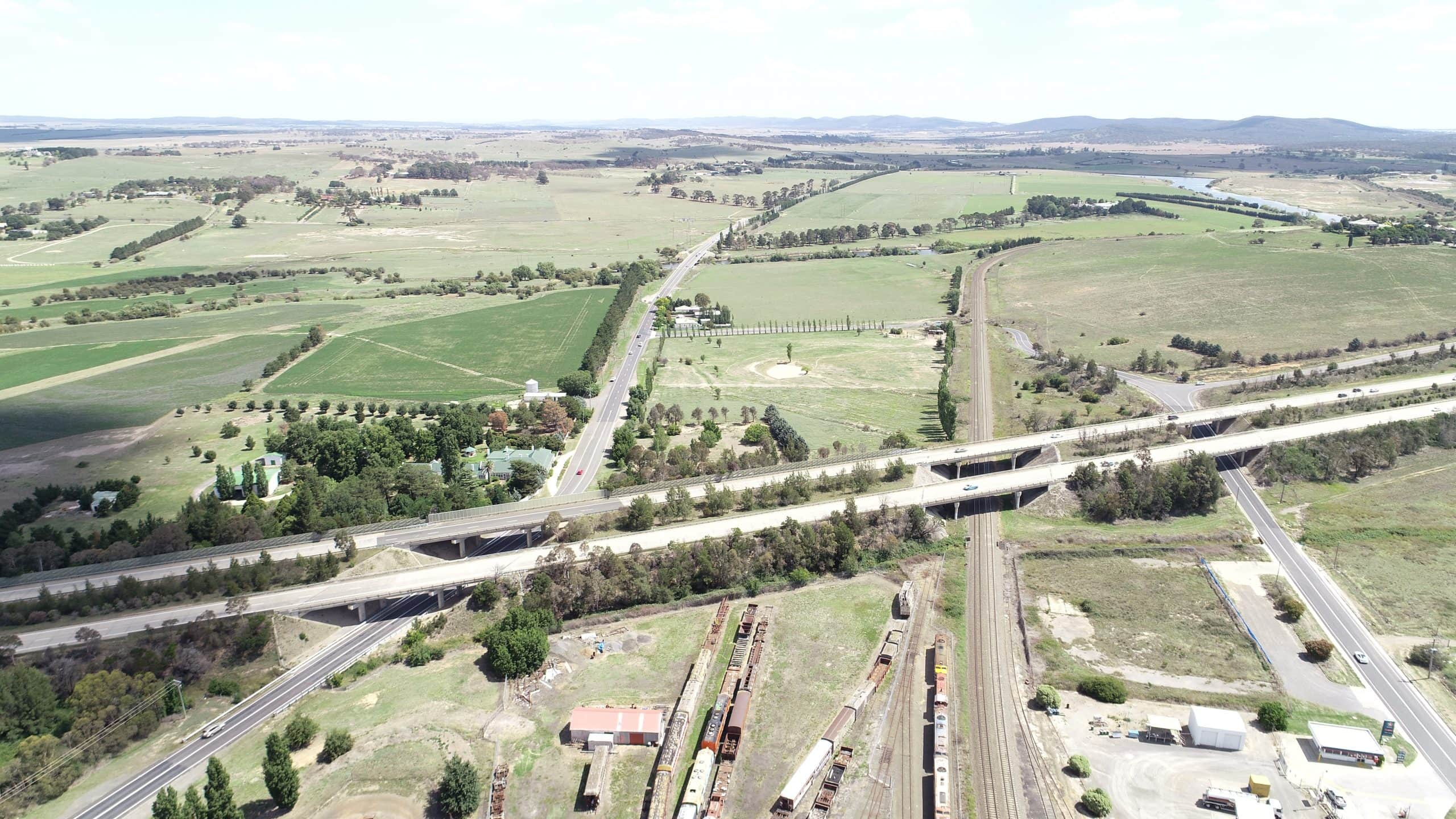 Aerial view of highway, railway, and freight trains of NSW, Australia